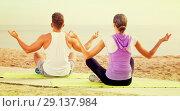 Купить «Cross-legged couple practice yoga on beach in morning», фото № 29137984, снято 22 октября 2018 г. (c) Яков Филимонов / Фотобанк Лори