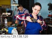 Купить «Portrait of girl worker who is holding adjustable wrench in workshop.», фото № 29138120, снято 10 октября 2017 г. (c) Яков Филимонов / Фотобанк Лори