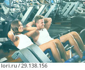 Купить «man and woman making sit ups together using machine in gym», фото № 29138156, снято 4 октября 2016 г. (c) Яков Филимонов / Фотобанк Лори