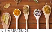 Купить «spoons with different spices on wooden table», видеоролик № 29138408, снято 20 сентября 2018 г. (c) Syda Productions / Фотобанк Лори