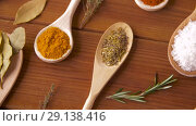 Купить «spoons with different spices on wooden table», видеоролик № 29138416, снято 20 сентября 2018 г. (c) Syda Productions / Фотобанк Лори
