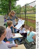 Купить «Преподаватель учит детей рисовать жирафа. Детский пленэр в зоопарке», фото № 29139104, снято 26 июня 2018 г. (c) Ирина Борсученко / Фотобанк Лори
