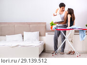Купить «The young woman doing ironing for her husband», фото № 29139512, снято 27 июня 2018 г. (c) Elnur / Фотобанк Лори