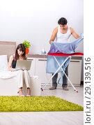 Купить «The man ironing, his lazy wife sitting», фото № 29139516, снято 27 июня 2018 г. (c) Elnur / Фотобанк Лори