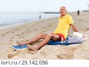 Купить «Satisfied cheerful man sitting on the sand», фото № 29142096, снято 16 июня 2018 г. (c) Яков Филимонов / Фотобанк Лори