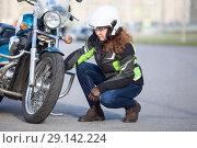 Купить «Девушка мотоциклистка осматривает переднее колесо мотоцикла», фото № 29142224, снято 15 сентября 2018 г. (c) Кекяляйнен Андрей / Фотобанк Лори