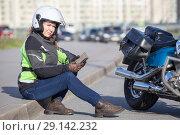 Купить «Девушка в мотоциклетной экипировке сидит на поребрике возле мотоцикла с телефоном в руках», фото № 29142232, снято 15 сентября 2018 г. (c) Кекяляйнен Андрей / Фотобанк Лори