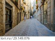 Купить «Туристы идут по узкой улочке в историческом центре Жироны, Испания», фото № 29149076, снято 11 сентября 2018 г. (c) Ольга Коцюба / Фотобанк Лори