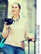 Купить «Smiling female is leafing through the booklet», фото № 29149096, снято 4 мая 2017 г. (c) Яков Филимонов / Фотобанк Лори