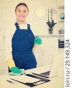 Купить «Smiling woman in protective uniform wiping surfaces», фото № 29149324, снято 21 января 2019 г. (c) Яков Филимонов / Фотобанк Лори