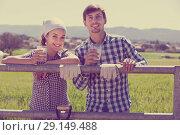 Купить «Young man and woman holding glass with milk», фото № 29149488, снято 18 апреля 2019 г. (c) Яков Филимонов / Фотобанк Лори