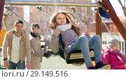 Купить «family with two girls having fun on swings outdoors», фото № 29149516, снято 23 февраля 2019 г. (c) Яков Филимонов / Фотобанк Лори