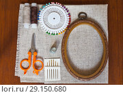 Купить «Accessories for needlework and sewing:  linen canvas, pins, needles, scissor and  frame for embroidery  on brown wooden table», фото № 29150680, снято 27 сентября 2018 г. (c) Виктория Катьянова / Фотобанк Лори