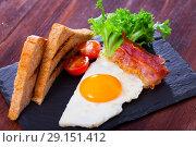 Купить «Fried eggs with bacon, toasted bread and tomatoes at plate, american breakfast», фото № 29151412, снято 18 октября 2018 г. (c) Яков Филимонов / Фотобанк Лори