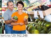 Купить «Adult male and female are choosing green melons in the store.», фото № 29162248, снято 22 октября 2017 г. (c) Яков Филимонов / Фотобанк Лори