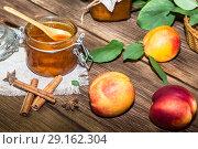 Купить «Food, sweet dessert. Homemade canning. Fruit peach jam in a jar and fresh ripe peaches against a wooden table in a rustic style», фото № 29162304, снято 9 сентября 2018 г. (c) Светлана Евграфова / Фотобанк Лори