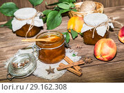 Food, sweet dessert. Homemade canning. A jar of fruit peach jam and fresh ripe peaches on a wooden table background in a rustic style. Стоковое фото, фотограф Светлана Евграфова / Фотобанк Лори