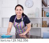 Купить «Smiling girl wiping table», фото № 29162356, снято 9 апреля 2017 г. (c) Яков Филимонов / Фотобанк Лори