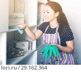 Купить «Smiling girl wiping shelves», фото № 29162364, снято 9 апреля 2017 г. (c) Яков Филимонов / Фотобанк Лори