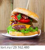 Купить «Double hamburger with beef, tomato, cheese, cucumber and lettuce», фото № 29162480, снято 16 октября 2018 г. (c) Яков Филимонов / Фотобанк Лори