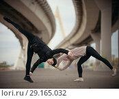 Купить «Girls begin to perform a synchronized jump in the splits on the urban background of the bridge», фото № 29165032, снято 2 октября 2018 г. (c) Константин Шишкин / Фотобанк Лори