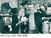 Купить «smiling young female and man choosing hats in the store», фото № 29165448, снято 2 мая 2017 г. (c) Яков Филимонов / Фотобанк Лори