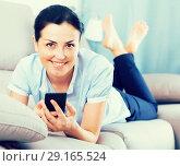 Купить «Cheerful female relaxation with phone», фото № 29165524, снято 2 июня 2017 г. (c) Яков Филимонов / Фотобанк Лори