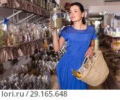 Купить «adult female choosing natural dried herbs sold by weight in eco shop», фото № 29165648, снято 13 июня 2017 г. (c) Яков Филимонов / Фотобанк Лори