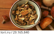 Купить «dried mushrooms in bowl on wooden background», видеоролик № 29165840, снято 30 сентября 2018 г. (c) Syda Productions / Фотобанк Лори