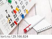 Купить «Отметки о мероприятиях на календаре, ручка и открытый блокнот. Деловой натюрморт», фото № 29166824, снято 13 сентября 2018 г. (c) Наталья Осипова / Фотобанк Лори