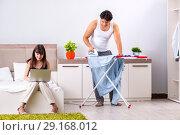 Купить «Man ironing, his lazy wife sitting», фото № 29168012, снято 27 июня 2018 г. (c) Elnur / Фотобанк Лори