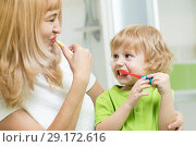 Купить «Beautiful mother and kid brushing teeth in bathroom», фото № 29172616, снято 27 марта 2019 г. (c) Оксана Кузьмина / Фотобанк Лори