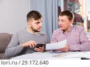 Купить «Focused males with phone and papers at home table», фото № 29172640, снято 7 февраля 2018 г. (c) Яков Филимонов / Фотобанк Лори