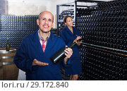 Купить «happy mature man winery worker looking at bottle of sparkling wine», фото № 29172840, снято 19 января 2019 г. (c) Яков Филимонов / Фотобанк Лори