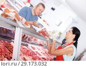 Купить «Woman seller helping male customer choosing meat», фото № 29173032, снято 22 июня 2018 г. (c) Яков Филимонов / Фотобанк Лори
