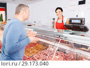 Купить «seller helping attentive customer choosing different sausages», фото № 29173040, снято 22 июня 2018 г. (c) Яков Филимонов / Фотобанк Лори
