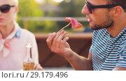 Купить «happy friends eating at bbq or rooftop party», видеоролик № 29179496, снято 26 сентября 2018 г. (c) Syda Productions / Фотобанк Лори