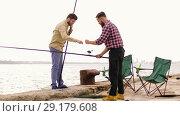 Купить «happy friends adjusting fishing rods on pier», видеоролик № 29179608, снято 28 сентября 2018 г. (c) Syda Productions / Фотобанк Лори