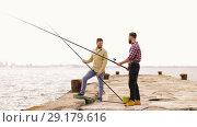 Купить «happy friends with fishing rods on pier», видеоролик № 29179616, снято 28 сентября 2018 г. (c) Syda Productions / Фотобанк Лори