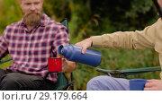 Купить «friends fishing and drinking tea from thermos», видеоролик № 29179664, снято 28 сентября 2018 г. (c) Syda Productions / Фотобанк Лори