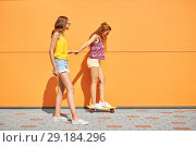 Купить «teenage girls riding skateboard on city street», фото № 29184296, снято 19 июля 2018 г. (c) Syda Productions / Фотобанк Лори