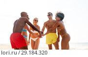 Купить «happy friends stacking hands on summer beach», фото № 29184320, снято 29 июля 2018 г. (c) Syda Productions / Фотобанк Лори