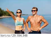 Купить «happy couple in sports clothes and shades on beach», фото № 29184348, снято 1 августа 2018 г. (c) Syda Productions / Фотобанк Лори