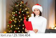 Купить «smiling woman with greeting card on christmas», фото № 29184404, снято 15 августа 2013 г. (c) Syda Productions / Фотобанк Лори