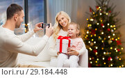 Купить «man taking picture of his family on christmas», фото № 29184448, снято 8 октября 2015 г. (c) Syda Productions / Фотобанк Лори