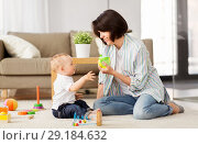 Купить «happy mother giving sippy cup to baby son at home», фото № 29184632, снято 12 мая 2018 г. (c) Syda Productions / Фотобанк Лори