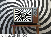 Propaganda and brainwashing of the influential mass media concept. Vintage TV set with hypnotic spiral on the screen. Стоковое фото, фотограф Maksym Yemelyanov / Фотобанк Лори