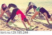 Купить «Sporty people practicing yoga on beach», фото № 29185244, снято 14 июня 2017 г. (c) Яков Филимонов / Фотобанк Лори