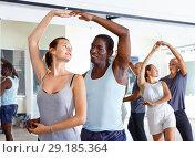 Купить «Young smiling people practicing passionate samba in dance class», фото № 29185364, снято 30 июля 2018 г. (c) Яков Филимонов / Фотобанк Лори