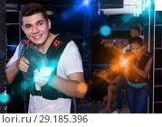 Купить «Excited guy holding laser pistol, playing laser tag with friends», фото № 29185396, снято 27 августа 2018 г. (c) Яков Филимонов / Фотобанк Лори